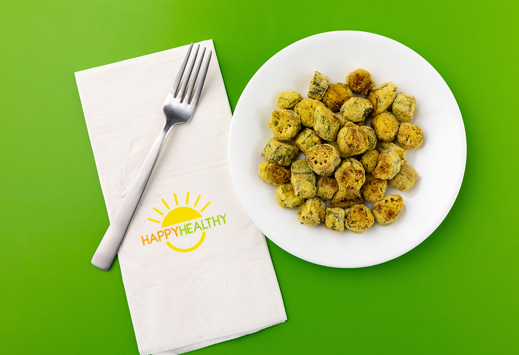 Fried okra bites on a white plate next to a HappyHealthy Napkin and Fork