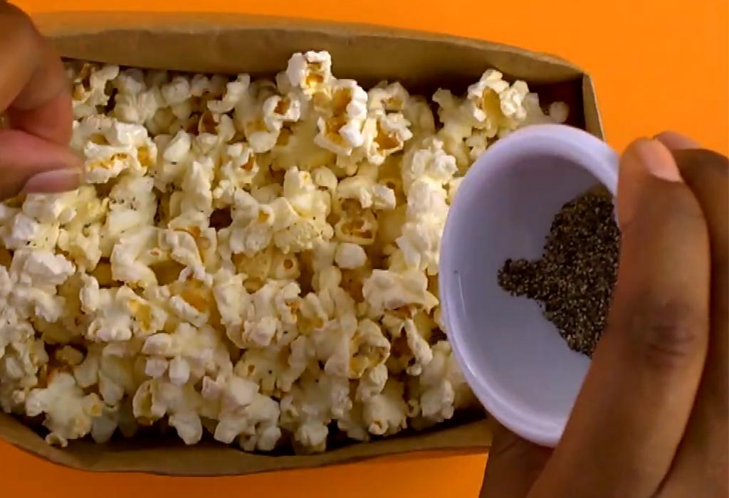 Bag of popcorn with hand adding seasoning