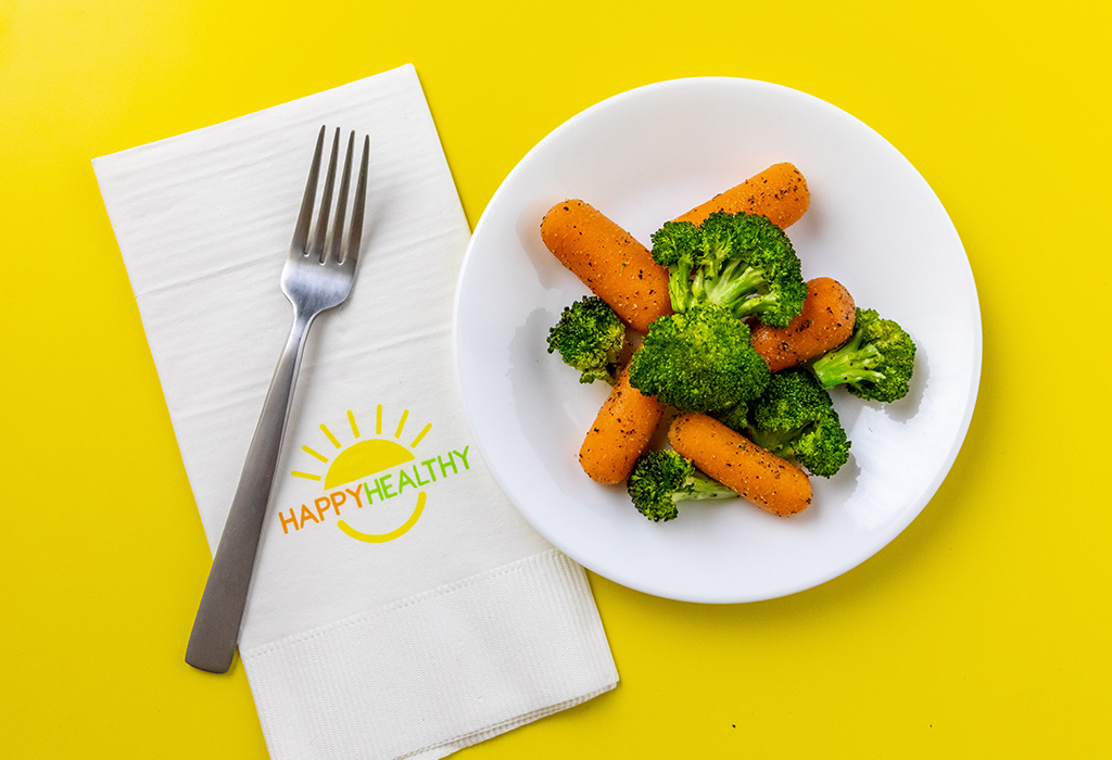 A plate of roasted broccoli and carrots next to a fork and Happy Healthy napkin