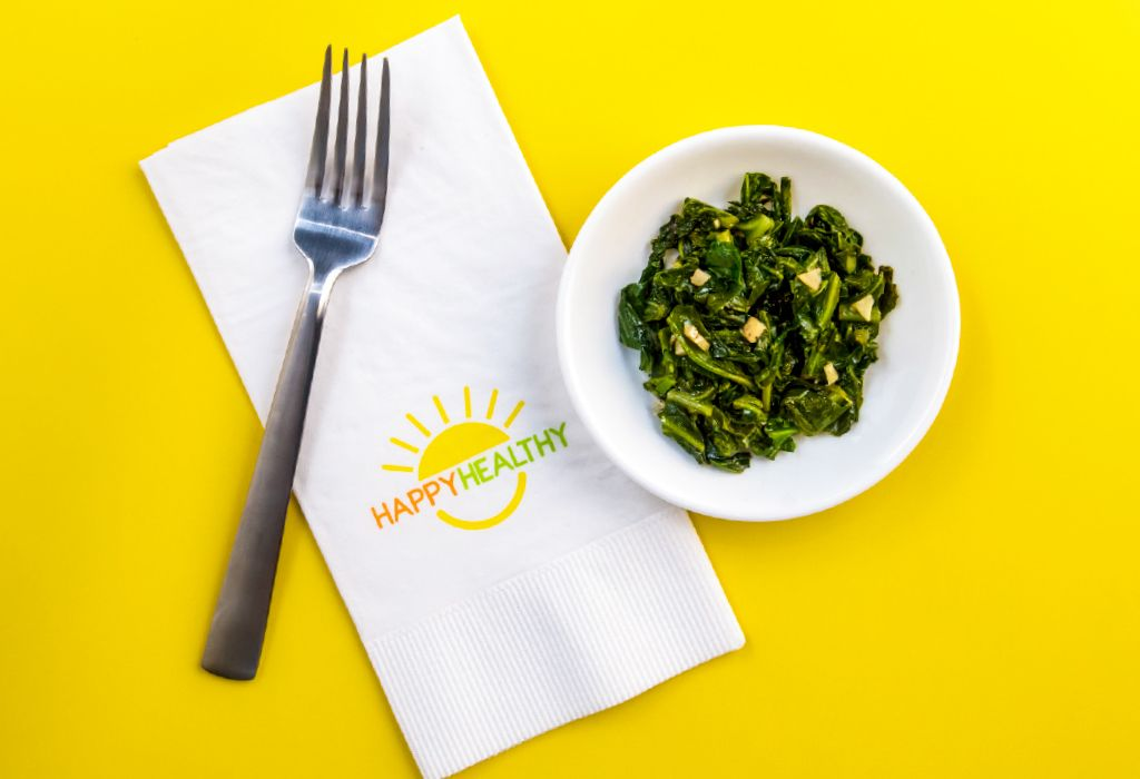 A plate of cooked greens, a fork, and a napkin stamped with the Happy Healthy logo.