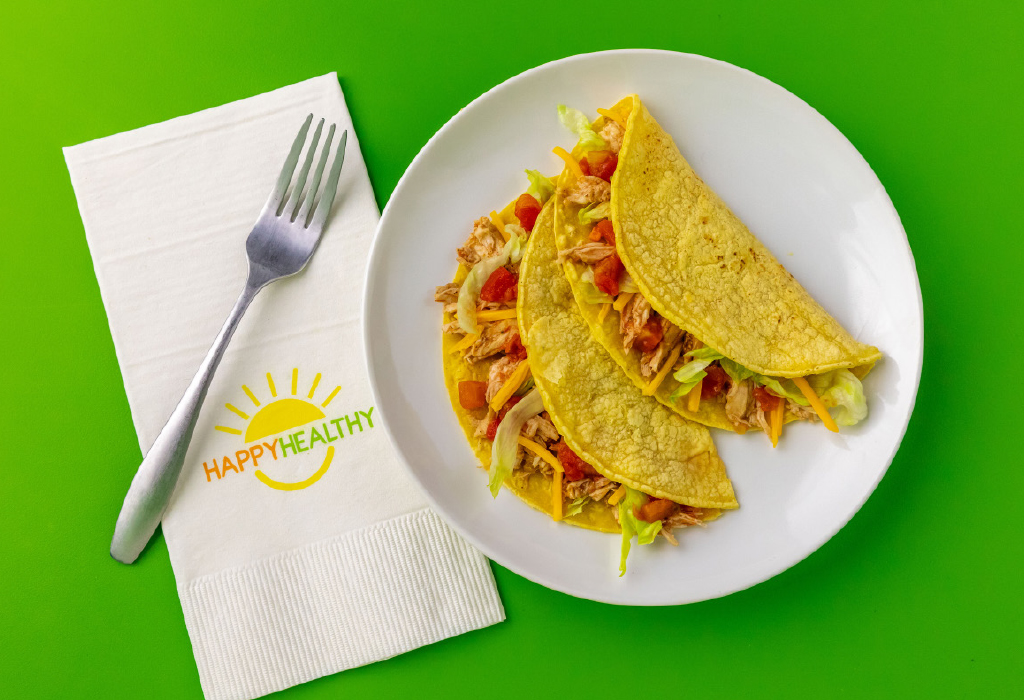 Two Slow Cooker Chicken Tacos on white plate next to HappyHealthy napkin with fork