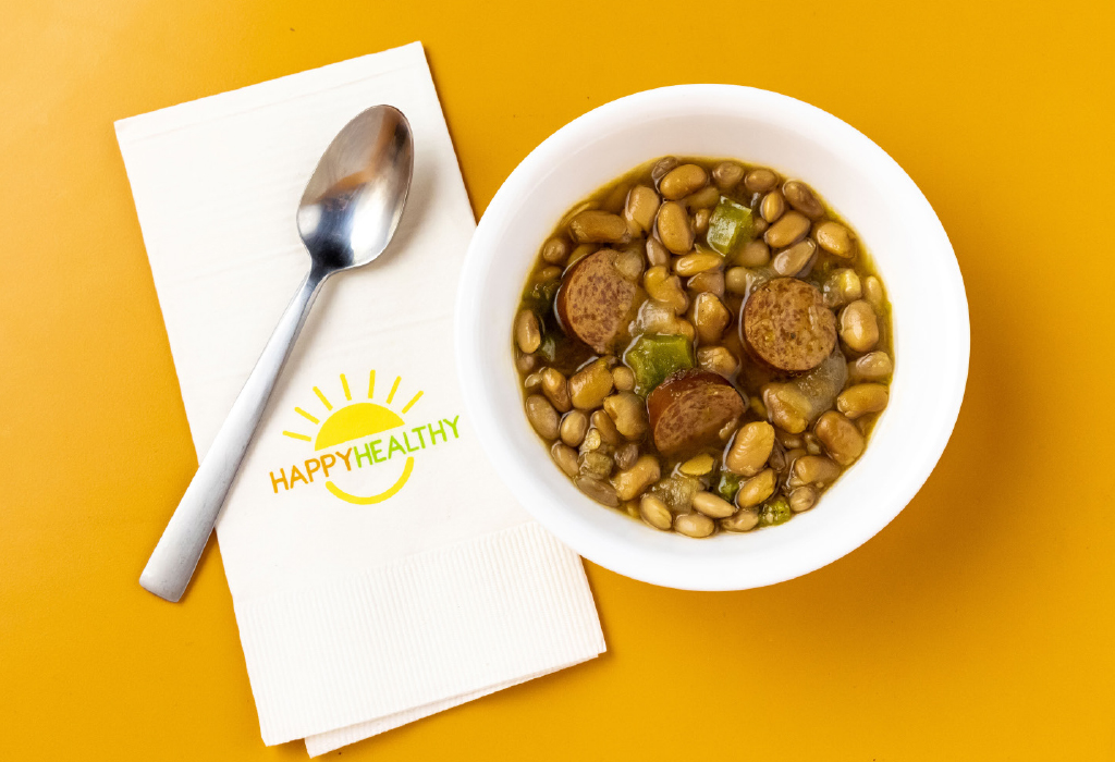 A bowl of slow cooker pinto beans next to a spoon and HappyHealthy napkin