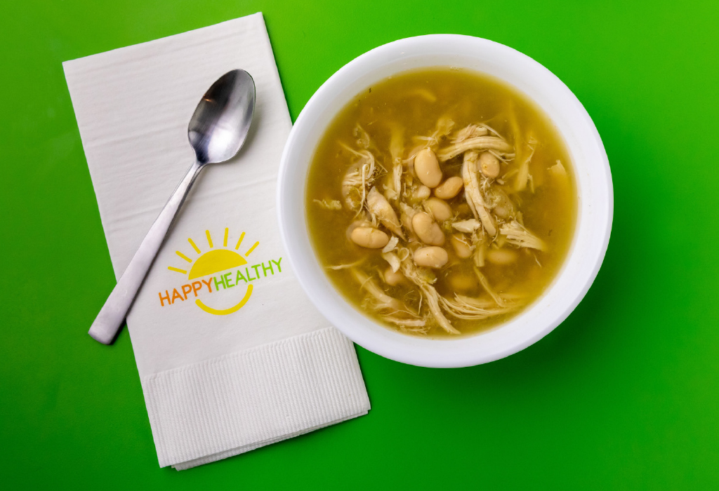 White chicken chili in white bowl next to HappyHealthy napkin and spoon.
