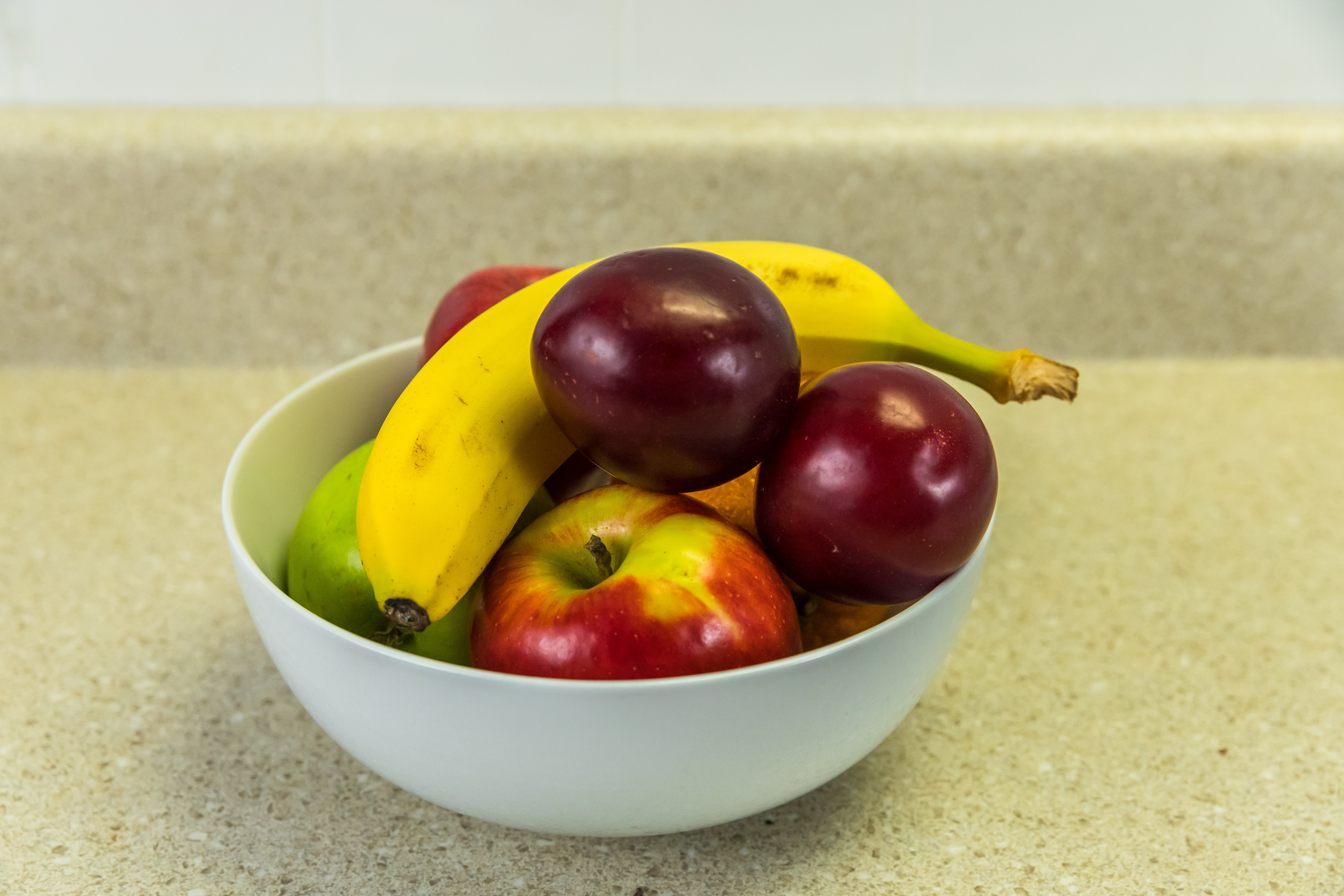 Banana and apples in a white bowl on a counter.