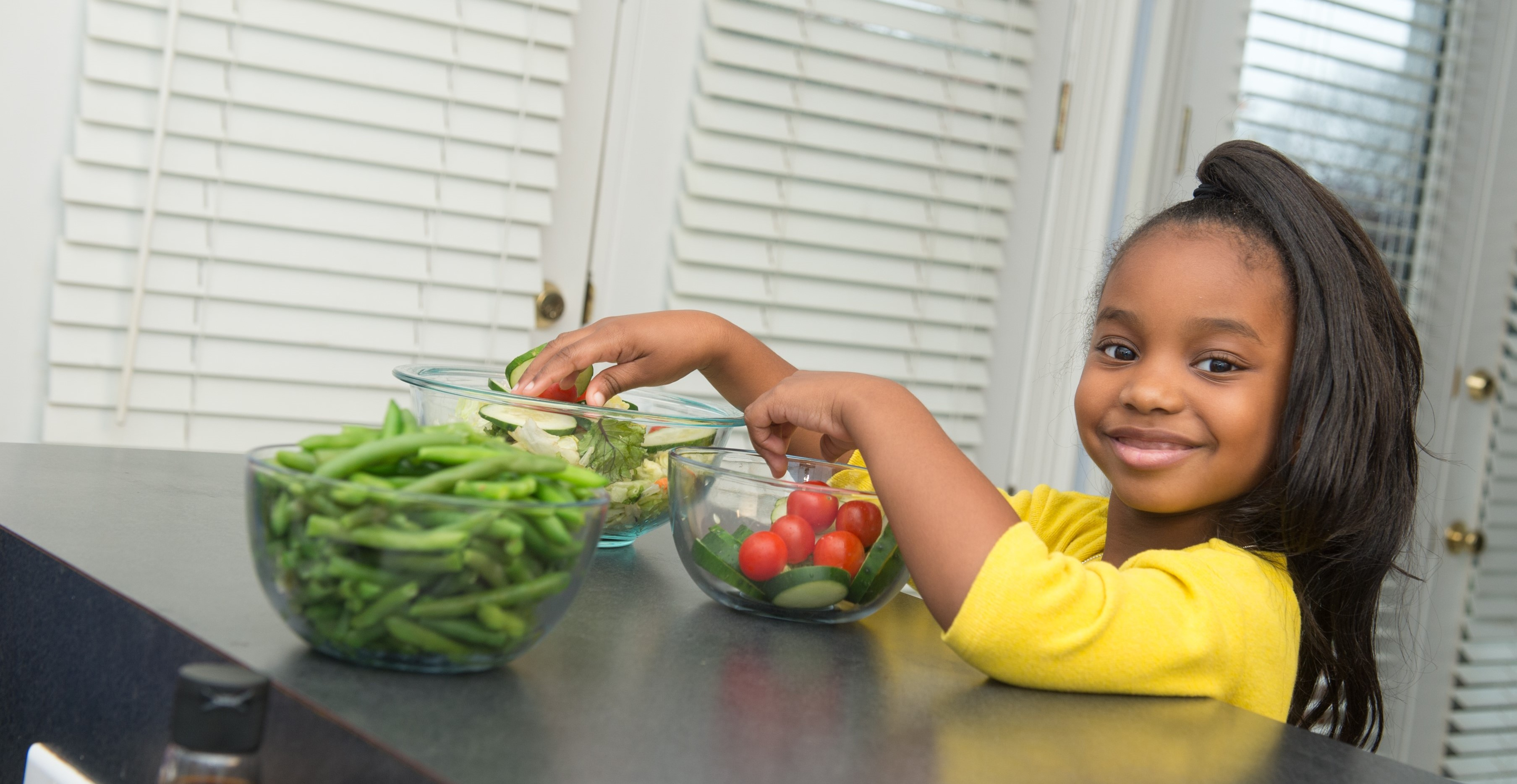 Young girl smiling with a bowl of vegetables.