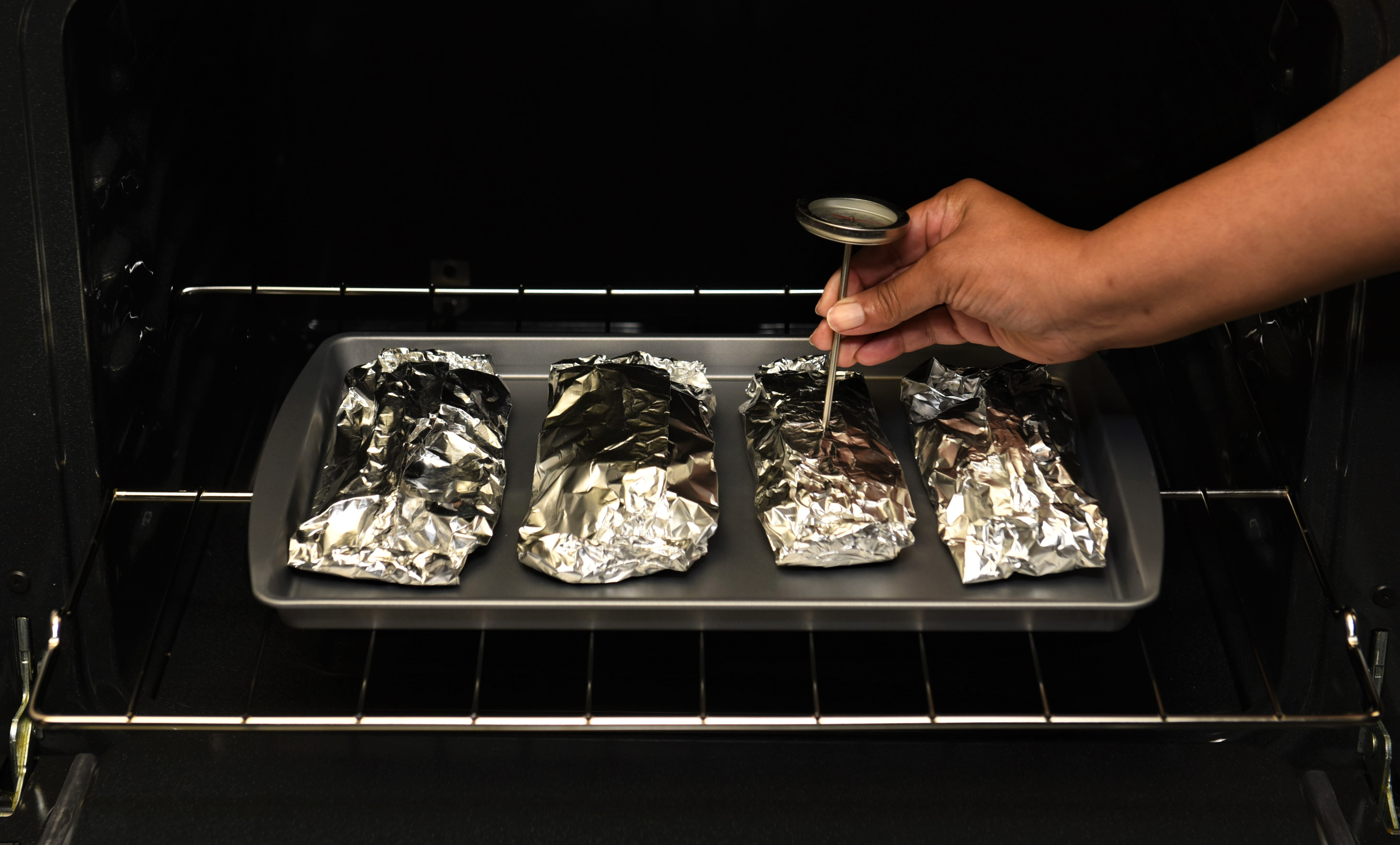 Four foil pouches on a baking sheet in an oven with a woman testing the temperature of one.