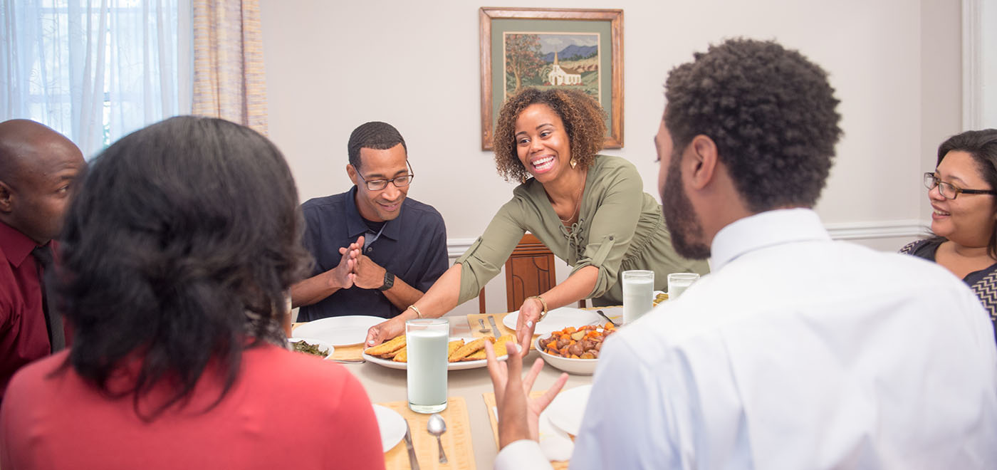 A happy family of three men and two women sit at a dinner table filled with oven-baked catfish filets, roasted potatoes, and a bowl of greens.
