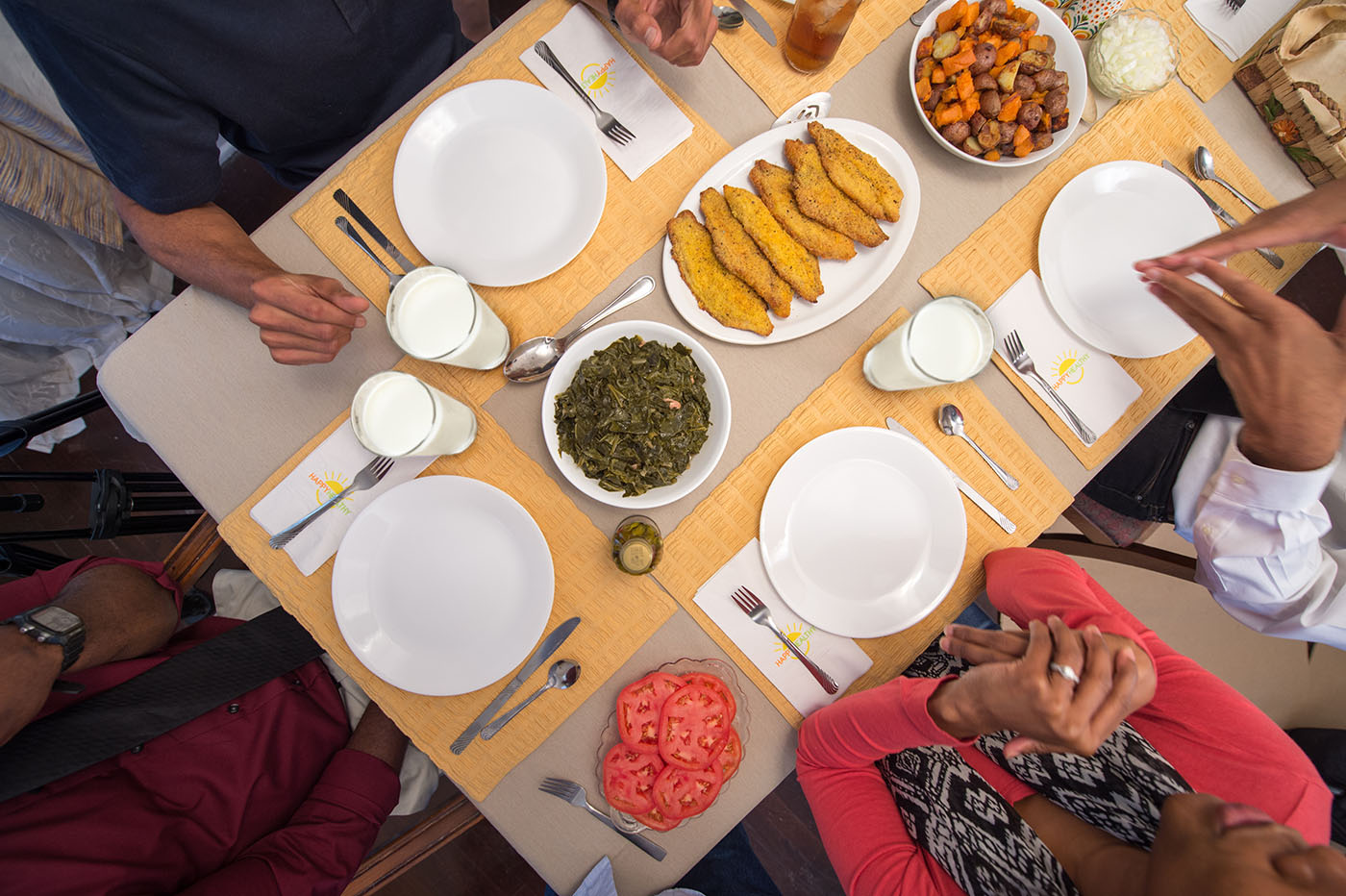 A family sitting around a set table with sliced tomatoes, greens, catfish and roasted potatoes in the center.