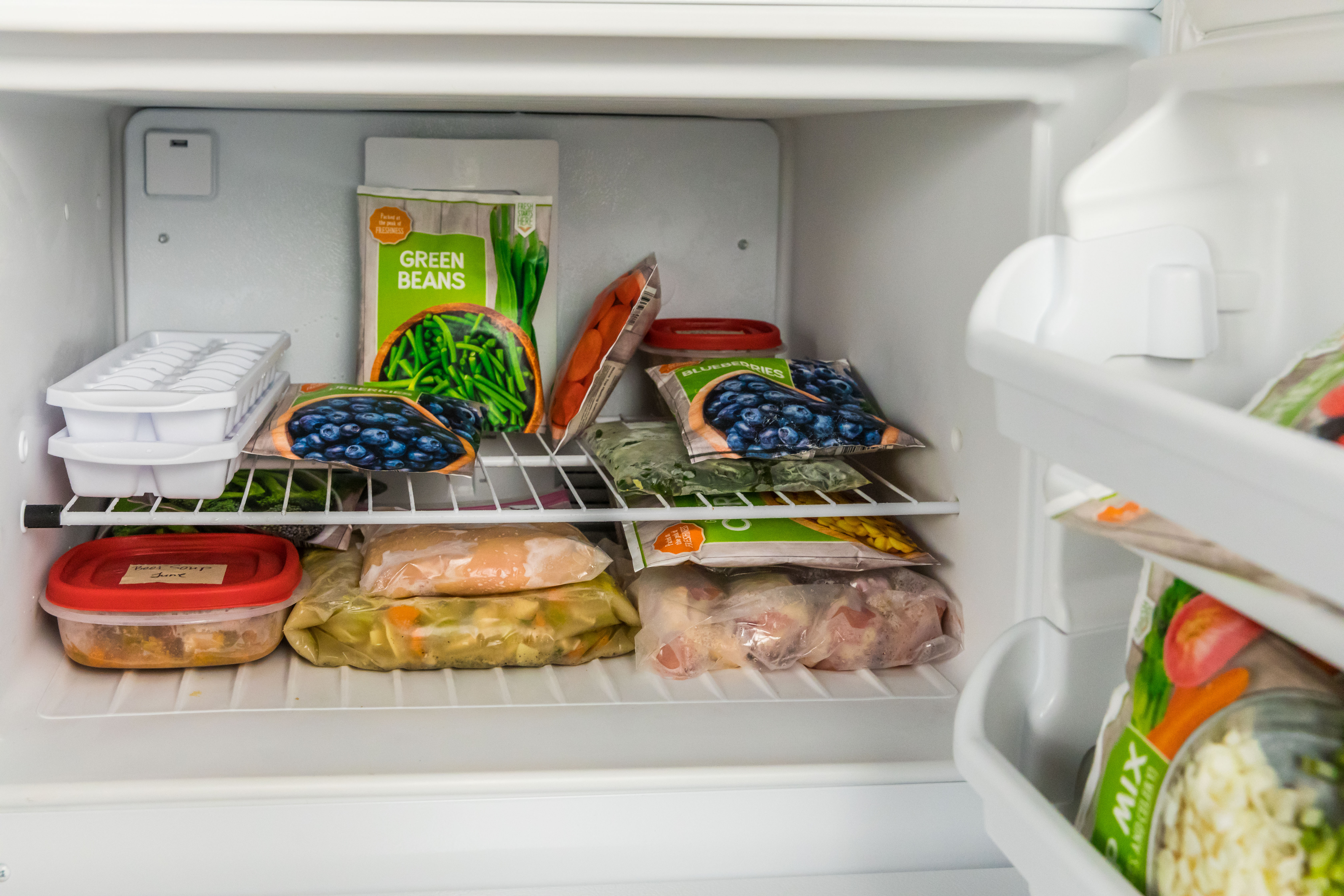 Food placed in containers in freezer with other pre-packaged frozen food items.