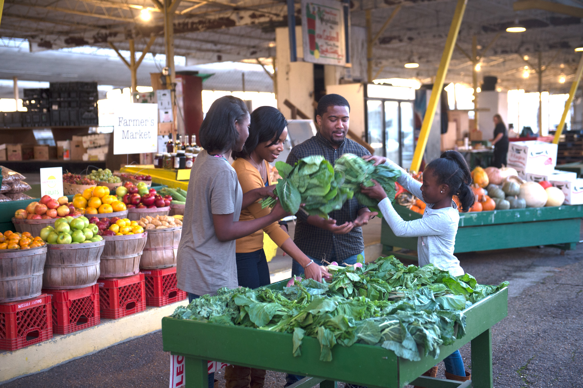 Family choosing greens at Farmer's Market.