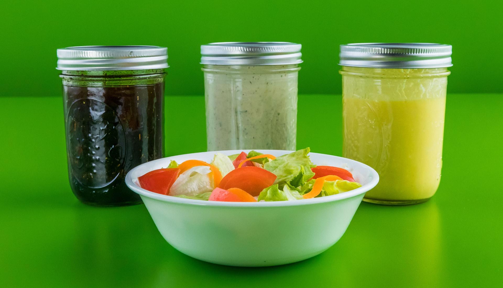 Three jars of salad dressing placed behind a bowl of salad