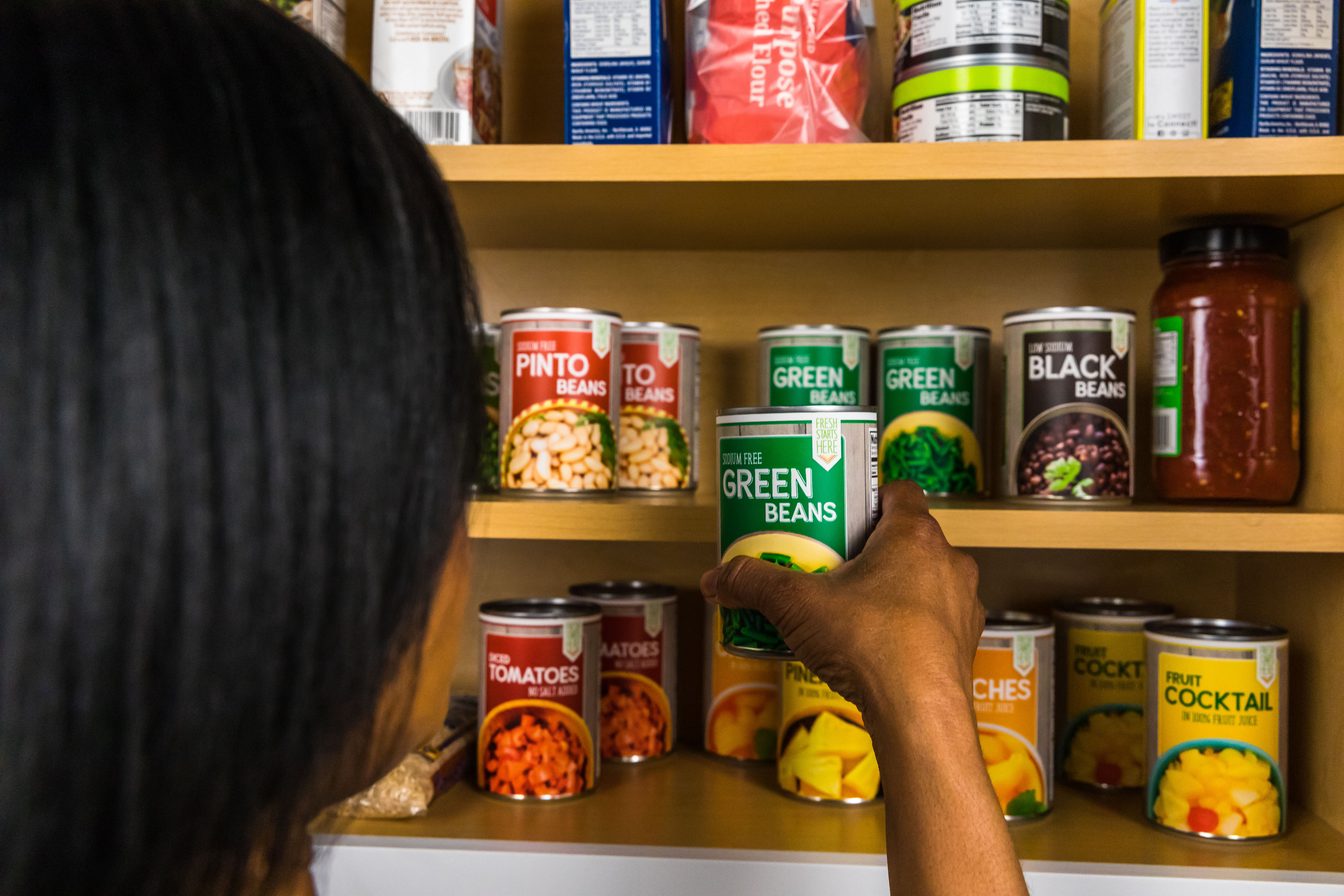 Woman placing canned item in pantry