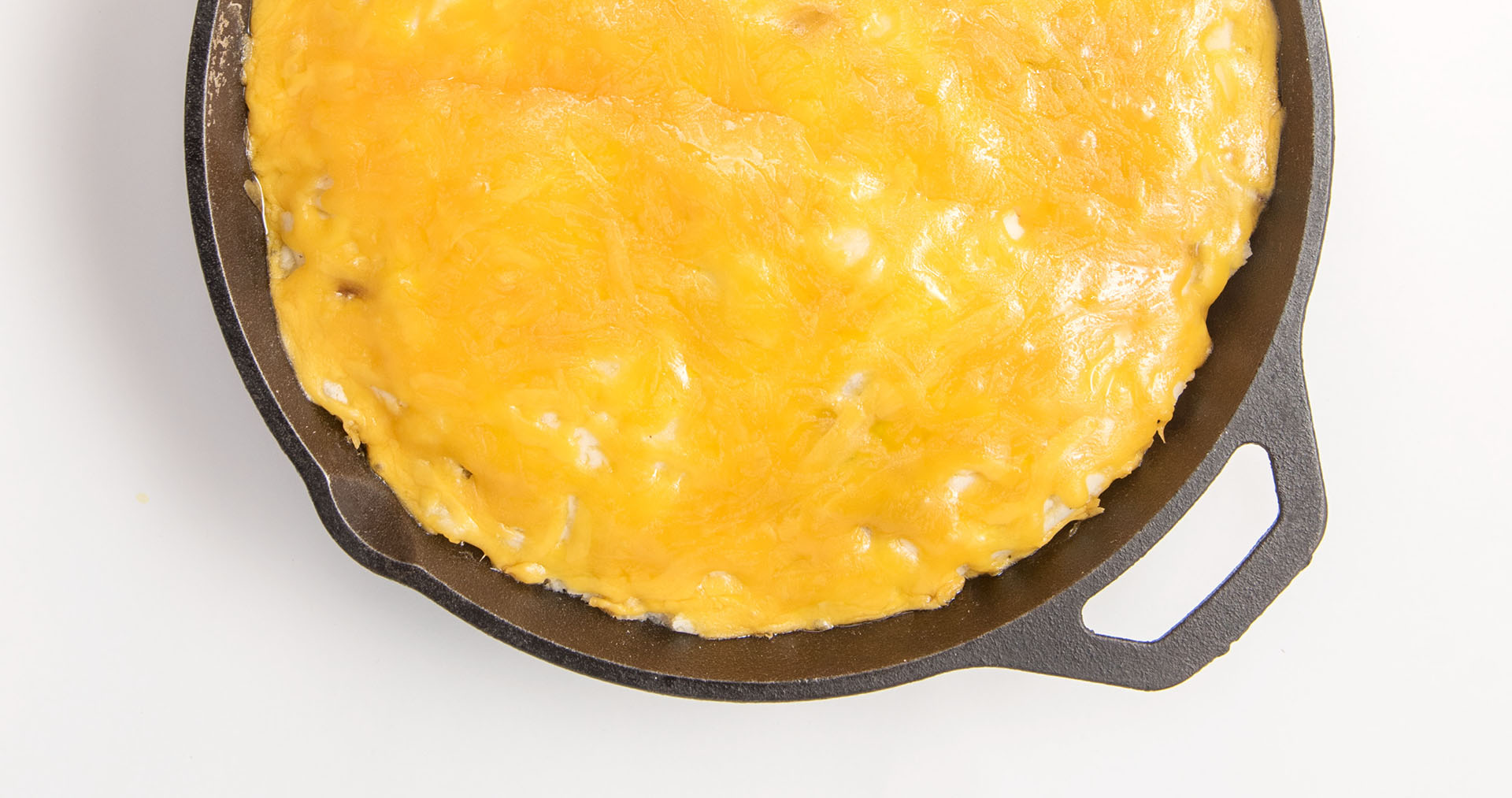 An iron skillet filled with Shepherd's Pie; a recipe using ground beef, green beans, mashed potatoes, and cheese.