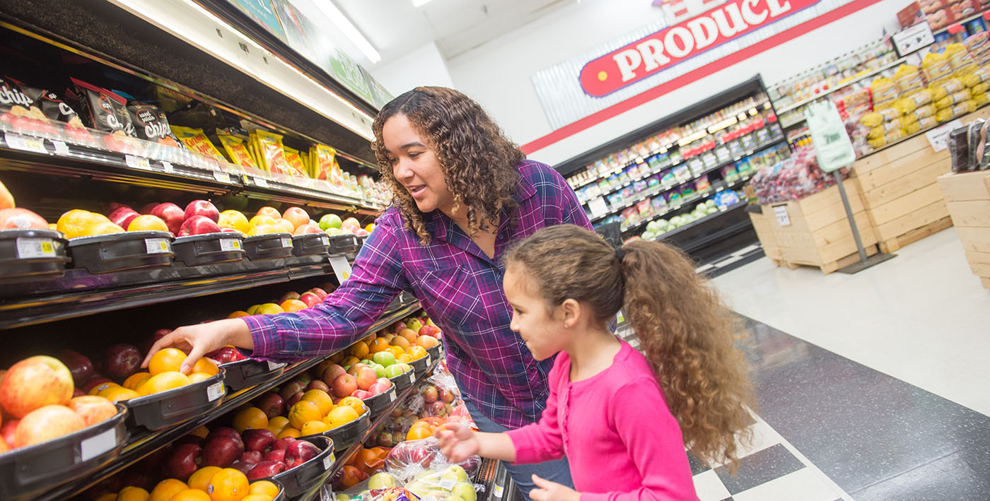 A woman and young girl shop for fruit in a grocery store.
