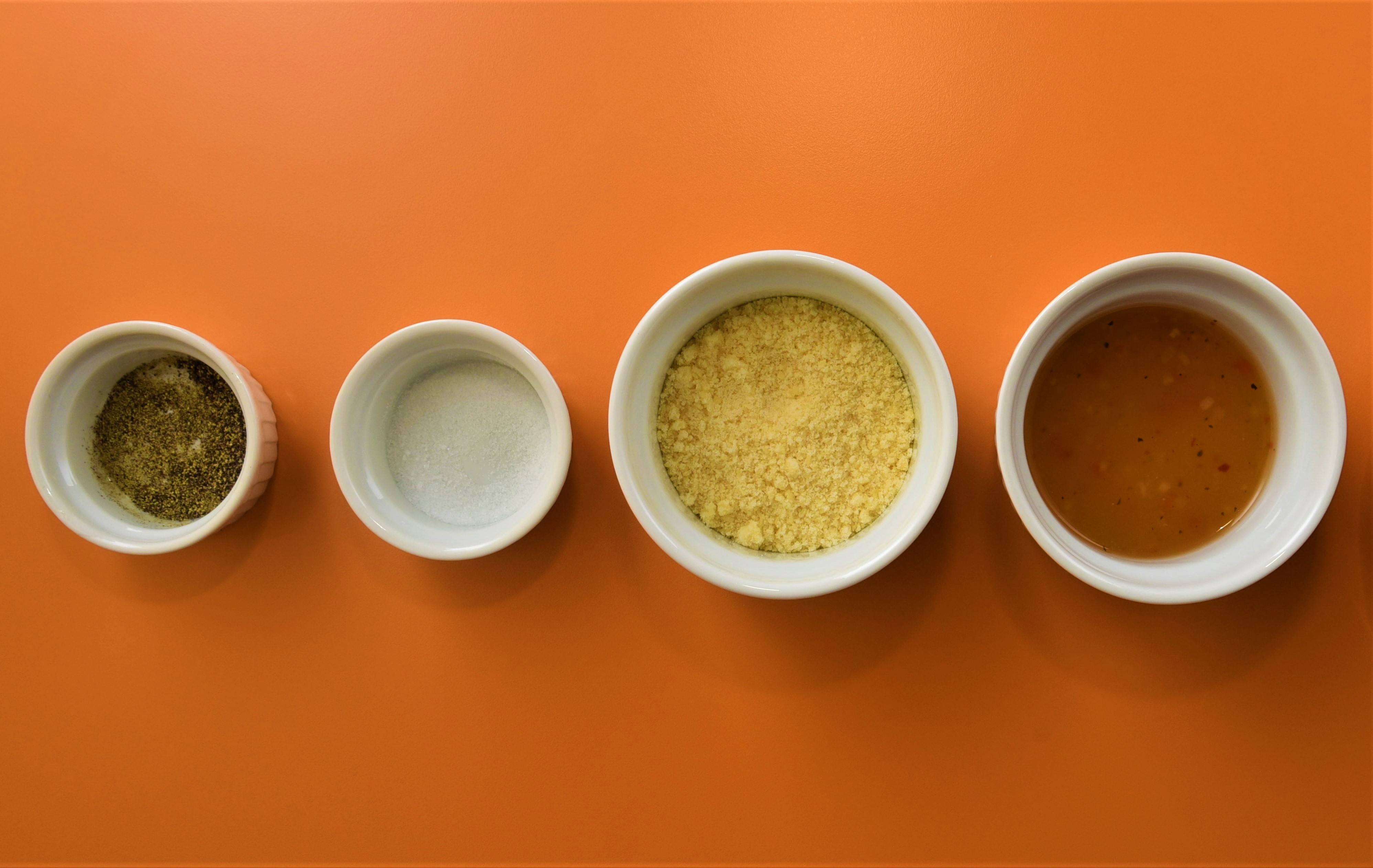 A different herb or spice in five bowls.