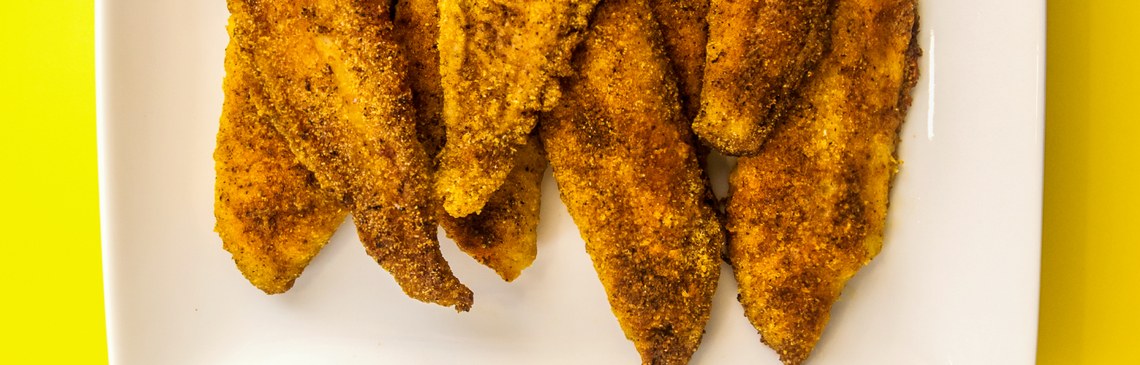 Plate with several cooked, seasoned catfish fillets