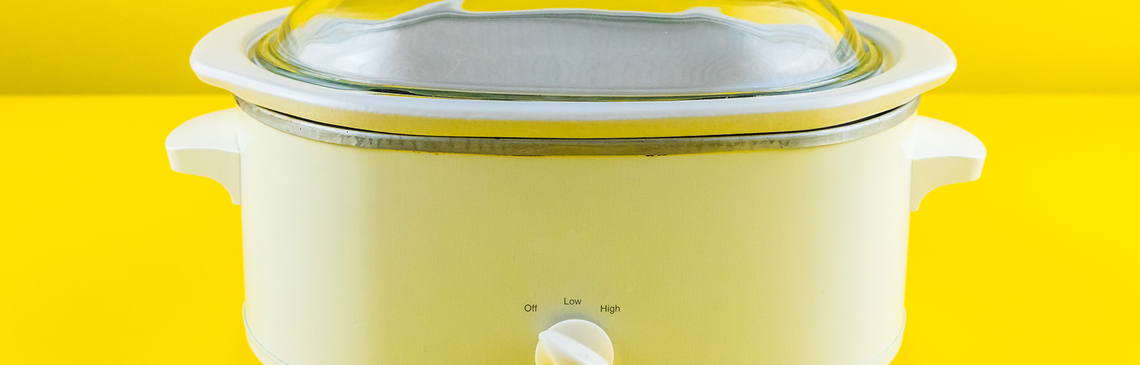 White slow cooker with yellow background.