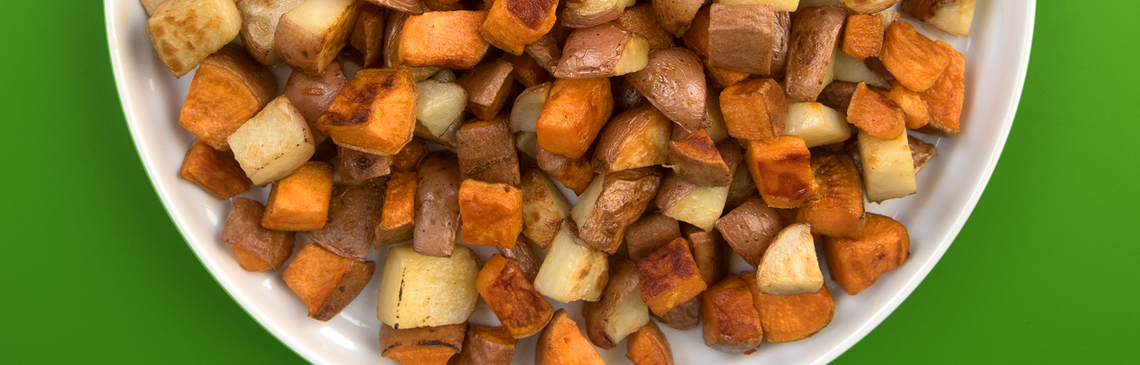 Cubed and roasted Irish and sweet potatoes on a white serving platter.
