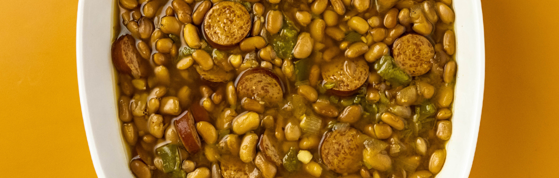 A white bowl filled with slow cooker pinto beans on an orange background