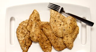 grilled chicken breast and a silver fork on a white platter.