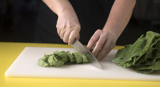 A woman cutting washed, leafy greens that have been rolled for slicing on a white cutting board.
