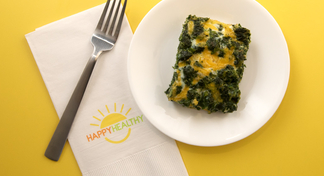 A serving of egg and spinach casserole on a white plate with a fork and napkin to the side.