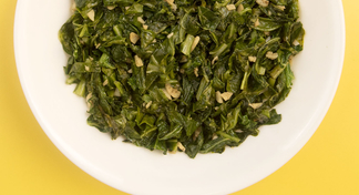 A white plate filled with cooked greens.