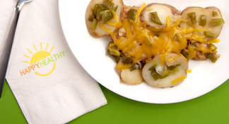 Plate with BBQ chicken, potato slices, and onions covered with cheese beside a napkin and fork