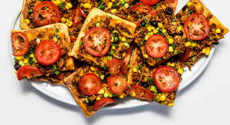 Platter with square pizza slice covered with tomatoes, olives, onions, beef, corn, and cheese