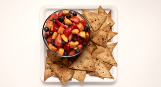 plate with tortilla chips and bowl of fruit salsa
