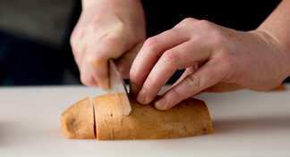 Hands chopping sweet potato on chopping board with knife