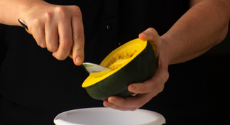hands scooping out squash over a bowl.