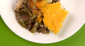 A white plate filled with Shepherd's Pie; a recipe using ground beef, green beans, mashed potatoes, and cheese.