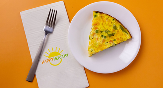 Slice of Anytime Egg Skillet on white plate next to HappyHealthy napkin and fork
