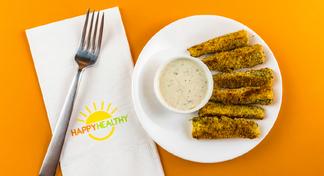 Plate with zucchini sticks and cup of low-fat ranch dressing beside a napkin and fork.