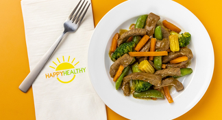 Beef Stir Fry in white bowl next to HappyHealthy napkin and fork