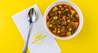 Beef Vegetable Soup with a spoon on a HappyHealthy napkin.
