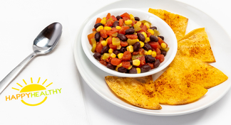 Black Bean and Corn Salsa in white bowl on white plate with chips, next to HappyHealthy napkin and spoon