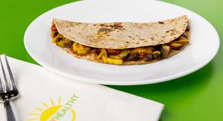 Black Bean & Vegetable Quesadilla on white plate next to HappyHealthy napkin and fork