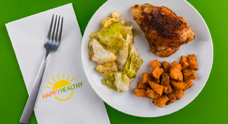 Blackened chicken with roasted vegetables on white plate with HappyHealthy napkin and fork to the side.