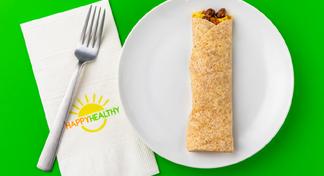 Breakfast Burrito on white plate next to HappyHealthy napkin and fork