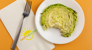 Cabbage steak on white plate next to HappyHealthy napkin and fork