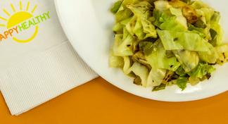 A plate filled with a serving of cabbage stir-fry with a HappyHealthy napkin to the side.