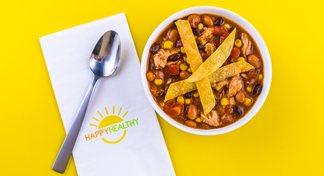 Bowl of Chicken Taco Soup with spoon on HappyHealthy napkin.