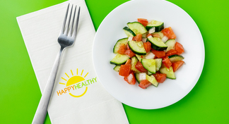 Cucumber Tomato Salad on white plate next to HappyHealthy napkin and fork