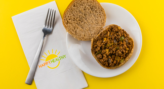 Easy Sloppy Joes (with bun) on a plate with a fork on a HappyHealthy napkin.