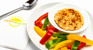 Bowl of hummus on white plate with spread of different colored peppers with HappyHealthy napkin and spoon to the side.