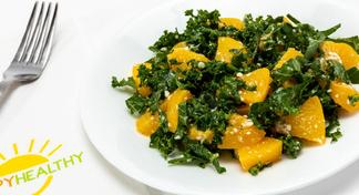 Kale salad on white plate next to HappyHealthy napkin and fork
