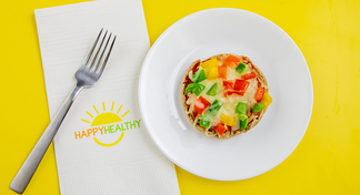 A single mini pizza on a white plate next to a Happy Healthy Napkin and Fork