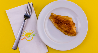 Fillet of Oven Blackened Catfish on white plate next to HappyHealthy napkin and fork